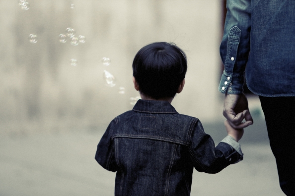 A child holding his parent's hand