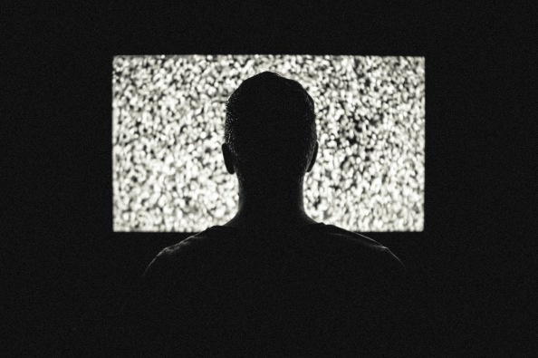 Man watching a static-filled television screen.