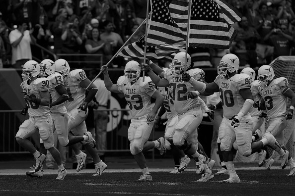 Football Players running with American Flag