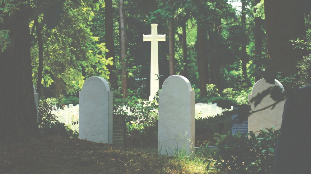 Gravestones amidst some woods with cross in the horizon