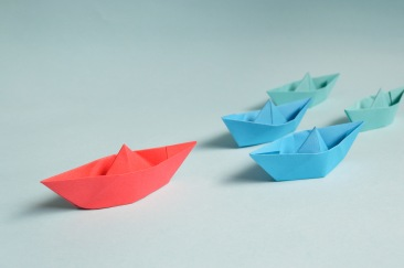 A red paper boat leading a group of blue paper boats.