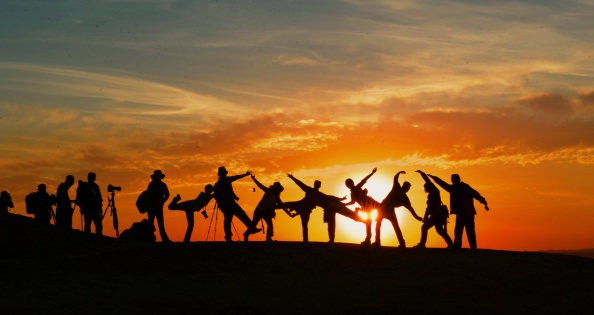 A silhouette of people against a sunset.