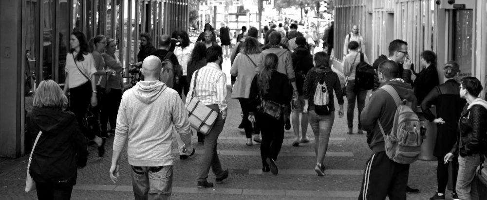 Black and white photo of a crowd walking away from viewer's perspective.