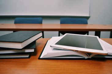 A close up of books and a tablet in a classroom.