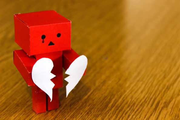 Image of a red cardboard character holding a ripped paper heart.